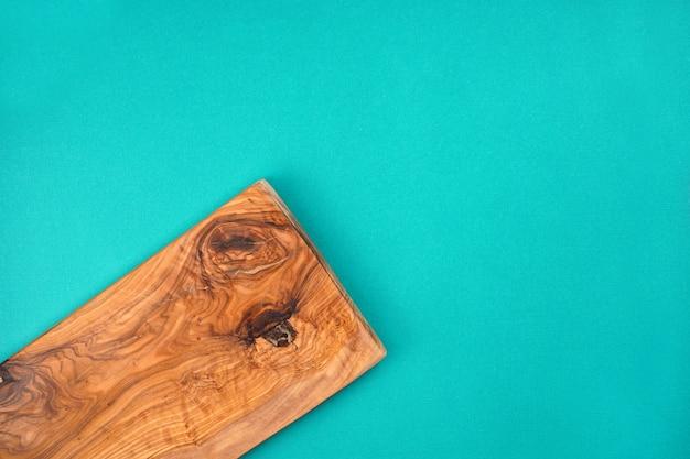 Drewniana tnąca deska od drzewa oliwnego na turkusowym tle