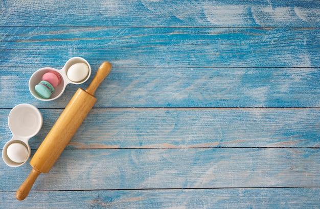 Drewniana toczna szpilka na błękitnym drewnianym stole.