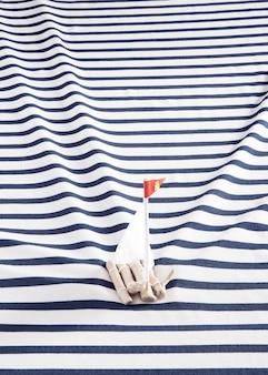 Drewniana tratwa z białymi żaglami na marynarskiej koszuli zamiast morza.