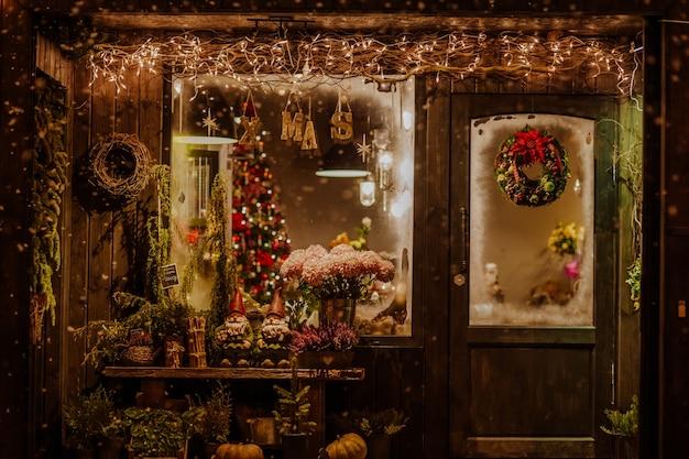 Drewniana weranda sklepu zdobiona dekoracją świąteczną z wieńcem na drzwiach