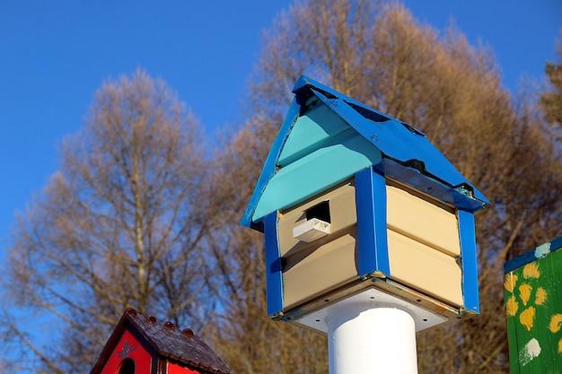 Drewniana, wielokolorowa budka dla ptaków w słoneczny wiosenny dzień. mały, jasny domek czeka na przybycie szpaków.