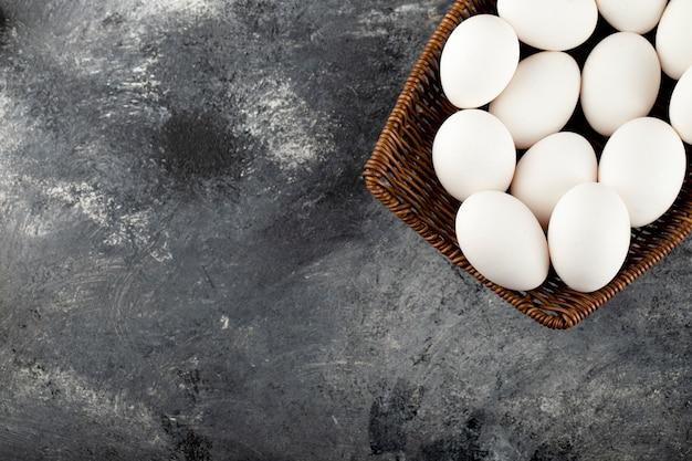 Drewniana wiklina pełna białych surowych jaj kurzych.