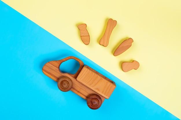 Drewniana zabawka ciężarówka z kością, marchewką, rybą, grzybami na na białym tle wielokolorowe tętniącego życiem tła geometrycznego