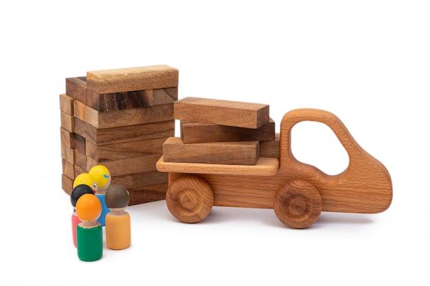 Drewniana zabawka ciężarówki przyniosła materiał budowlany w postaci kłód na plac budowy.