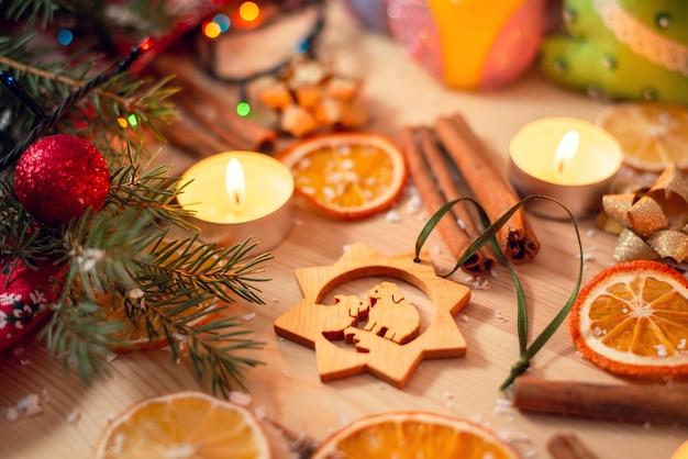 Drewniana zabawka do jodły na stole, otoczona różnymi dekoracjami świątecznymi