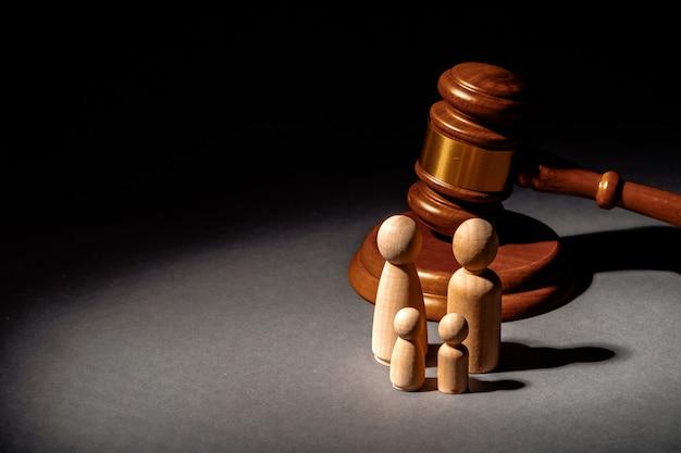 Drewniana zabawka rodzinna i sędzia młotek. pojęcie rozwodu rodzinnego