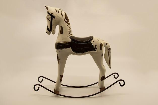 Drewniana zabawka w kształcie konia na biegunach na jasnym tle