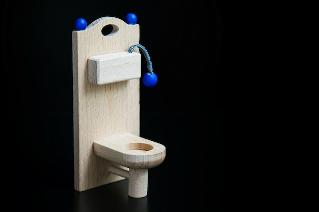 Drewniana zabawkowa toaleta na czerni
