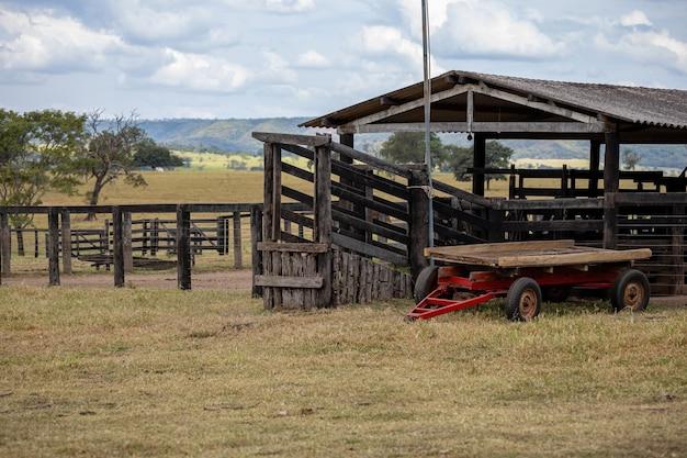 Drewniana zagroda do obsługi zwierząt gospodarskich w gospodarstwie z zaparkowanym ciągnikiem