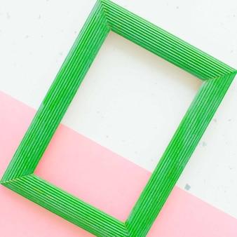 Drewniana zielona ramka na zdjęcia na białym i różowym tle