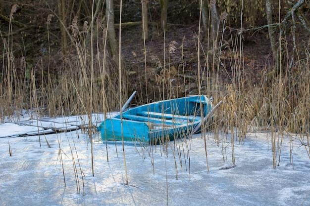 Drewniana zniszczona łódź nad zamarzniętym zimowym jeziorem. pojęcie życia towarzyskiego i samotności