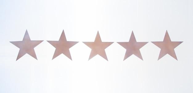 Drewniane 5 gwiazdek na białym tle. ocena usługi