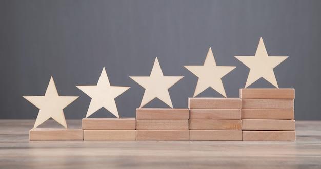 Drewniane 5 gwiazdek na drewnianym bloku. zwiększ ocenę