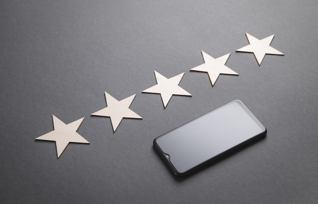 Drewniane 5 gwiazdek ze smartfonem. ocena usługi. doświadczenie klienta