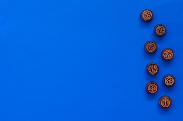 Drewniane beczki lotto na niebieskiej powierzchni. cocept z liczbami