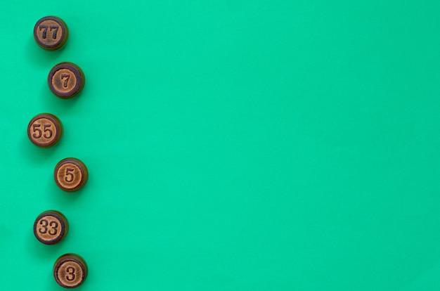 Drewniane beczki lotto na zielonym tle. pojęcie z liczbami