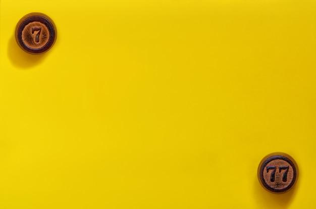 Drewniane beczki lotto na żółtej powierzchni. pojęcie z liczbami