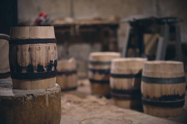 Drewniane beczki w starej piwnicy w winnicy. beczki na wino ze stalowym pierścieniem