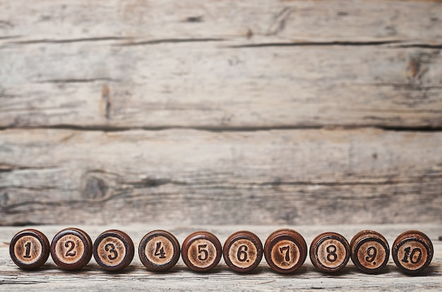 Drewniane beczki z numerami od jednego do dziesięciu na starym drewnianym tle.