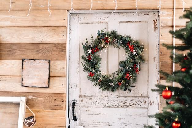 Drewniane białe drzwi do domu ozdobione wieńcem bożonarodzeniowym.