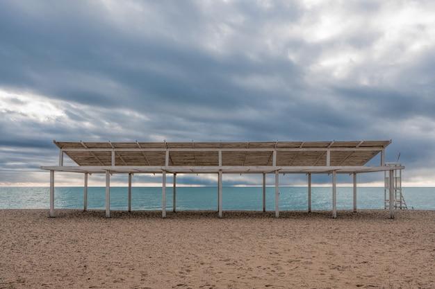 Drewniane białe parasole na pustej piaszczystej plaży z pochmurnego nieba. koniec sezonu letniego.