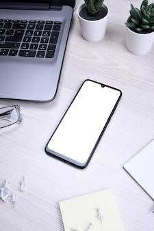 Drewniane biurko do pracy z pustym telefonem komórkowym, różne materiały eksploatacyjne.