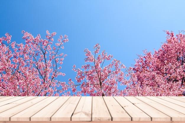 Drewniane biurko lub drewniana podłoga do ekspozycji produktów z różowym tłem sakura
