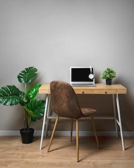 Drewniane biurko z krzesłem i szarym laptopem