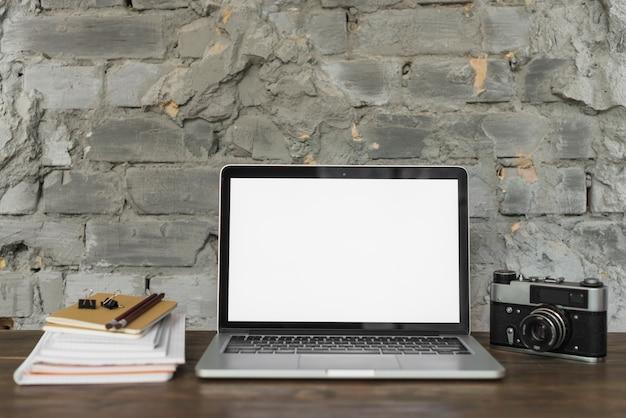 Drewniane biurko z laptopem; aparat retro i materiały piśmienne
