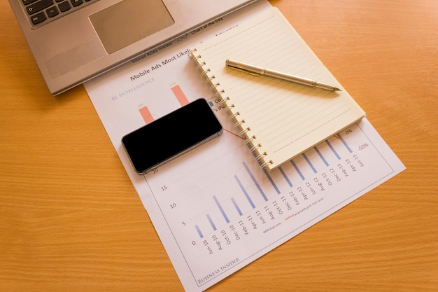 Drewniane biurko z laptopem, smartphone pióro notatnik.
