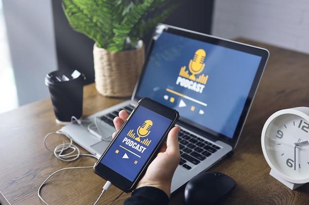 Drewniane biurko z laptopem z obsługą podcastów na ekranie. ręka trzyma smartfon z aplikacją podcast.