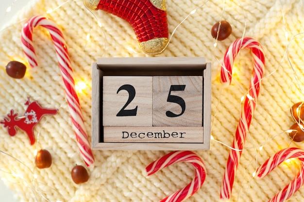 Drewniane bloki kalendarza ze słodyczami, girlandami i ozdobami świątecznymi. 25 grudnia data w kalendarzu.