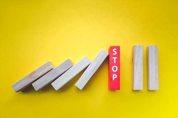 Drewniane bloki z tekstem stop zatrzymując spadające domino na żółtym. koncepcja kreatywna, logiczna