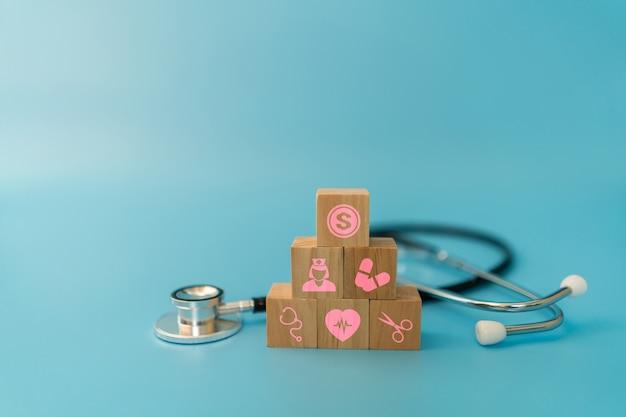Drewniane bloki z układaniem ikon opieki zdrowotnej i stetoskopem na niebieskiej przestrzeni, koncepcja ubezpieczenia medycznego opieki zdrowotnej