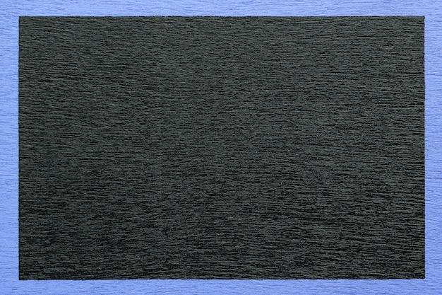 Drewniane czarne tło otoczone niebieską ramką.