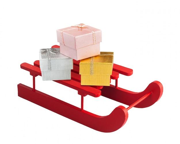 Drewniane czerwone sanki z pudełkami na prezenty