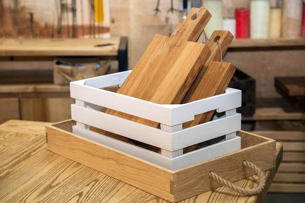 Drewniane deski do krojenia w pudełku na stole kuchennym