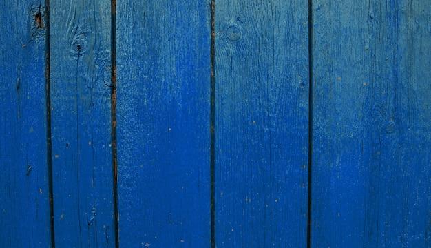 Drewniane deski malowane na niebiesko. szorstka i popękana powierzchnia. stare drewno i farba.
