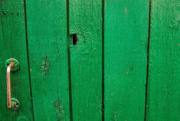 Drewniane deski są pomalowane na zielono. szorstka i popękana powierzchnia. stare drewno i farba.