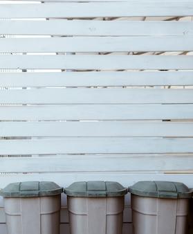 Drewniane deski tło z trzema plastikowymi koszami na śmieci, tło środowiskowe