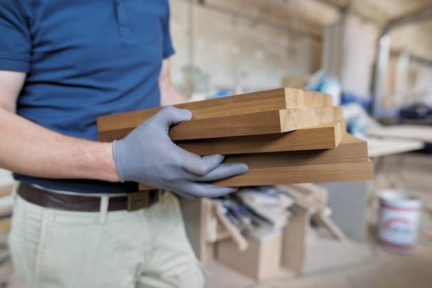 Drewniane detale meblowe w rękach stolarza, stolarnia stolarska w tle stolarskim