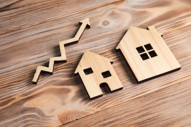 Drewniane domy i strzałka w górę. pojęcie wzrostu rynku nieruchomości