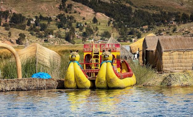 Drewniane domy i tradycyjne łodzie z trzciny totora na jeziorze titicaca puno peru ameryka południowa