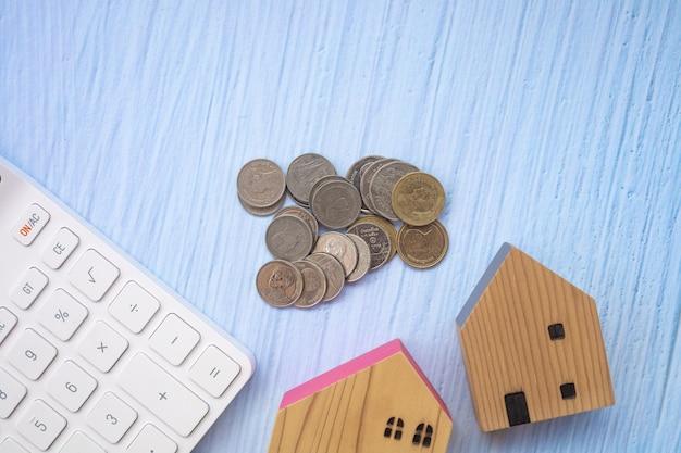 Drewniane domy, monety i biała klawiatura na niebieskim drewnianym tle