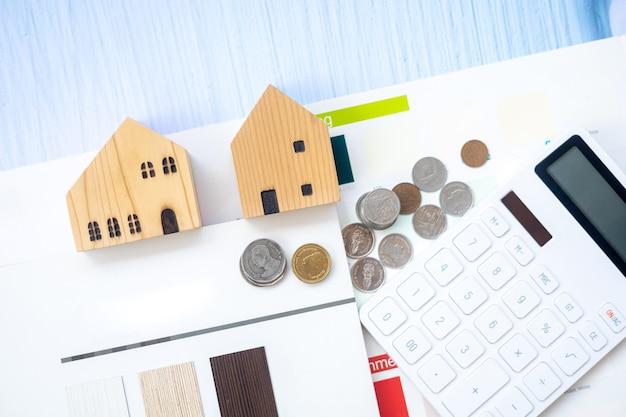 Drewniane domy, monety, kalkulator i papiery na niebieskim drewnianym tle