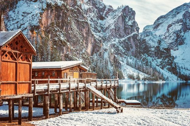Drewniane domy w śniegu na tle krystalicznie czystej wody jeziora braies w dolomitach, włochy. kolorowy zima krajobraz w śnieżnych włoskich alps, popularny punkt turystyczny we włoszech