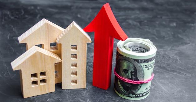 Drewniane domy z czerwoną strzałką w górę. koncepcja wysokiego popytu na nieruchomości.