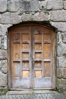 Drewniane drzwi na antycznej kamiennej ścianie. średniowieczny budynek