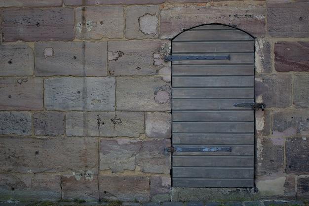 Drewniane drzwi przy kamiennej ścianie. spacer w pobliżu zamku