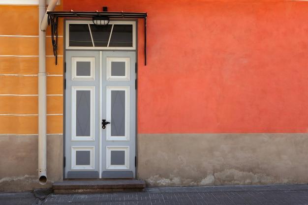 Drewniane drzwi z elementami dekoracyjnymi w starej elewacji budynku. tallin, estonia. kolorowe drewniane antyczne drzwi